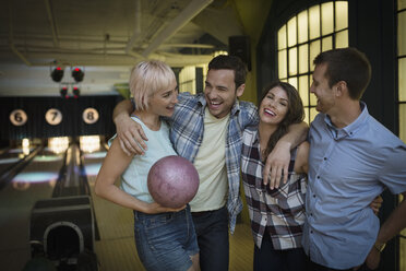 Friends hugging and laughing at bowling alley - HEROF27947