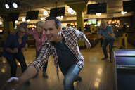 Man bowling with friends at bowling alley - HEROF27950