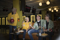 Friends in bowling shirts eating drinking bowling alley - HEROF27953