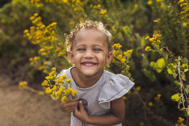High angle portrait of happy girl with holding flowers while standing plants in park - CAVF62903