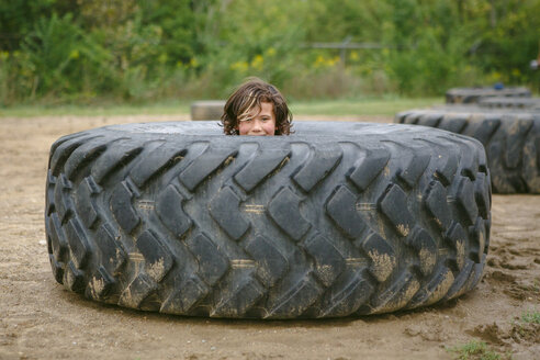 Portrait of cute boy peeking through dirty tire - CAVF62936