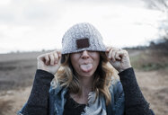 Close-up of playful woman covering eyes with knit hat sticking out tongue while standing on landscape against cloudy sky - CAVF63000