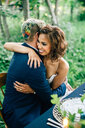 Bride and groom hugging at forest table - ISF20950