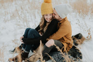 Happy couple sitting on snowy field - ISF20962