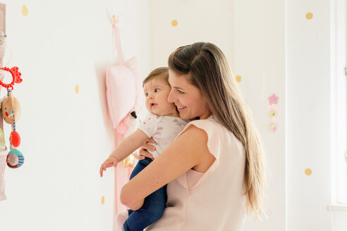 Mother hugging baby girl in room - ISF20977