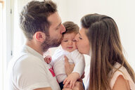 Parents kissing baby girl's cheeks at home - ISF20983