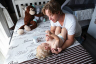 Father talking to baby boy on bed - ISF21007