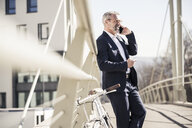 Smiling mature businessman with bicycle talking on cell phone in the city - UUF16618