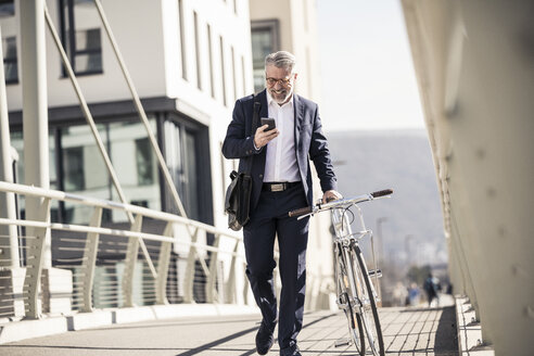 Smiling mature businessman with bicycle and cell phone in the city - UUF16621