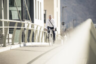 Smiling mature businessman riding bicycle on a bridge in the city - UUF16633