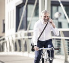 Happy mature businessman talking on cell phone and riding bicycle on a bridge in the city - UUF16636