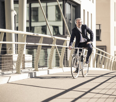 Smiling mature businessman with headphones riding bicycle on a bridge in the city - UUF16639