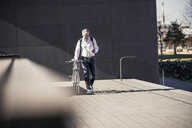 Mature businessman with bicycle using cell phone in the city - UUF16642