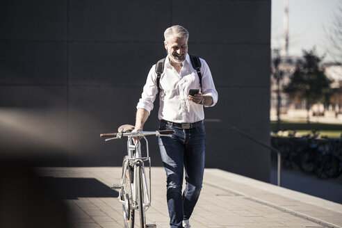 Smiling mature businessman with bicycle, cell phone and earphones on the go - UUF16645