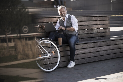 Smiling mature businessman with bicycle sitting on a bench using laptop - UUF16648