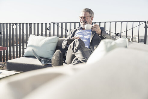 Smiling mature businessman with cup of coffee and tablet on roof terrace - UUF16684