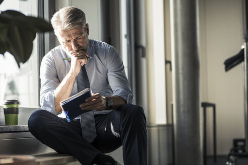 Mature businessman sitting at the window with notebook - UUF16702
