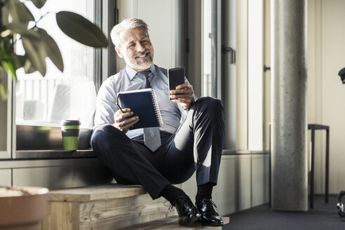 Smiling mature businessman sitting at the window with cell phone and notebook - UUF16705