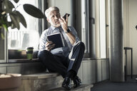 Mature businessman with notebook sitting at the window using cell phone - UUF16708