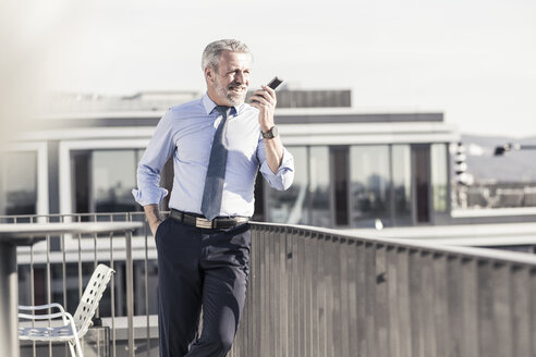 Smiling mature businessman using cell phone on roof terrace - UUF16711