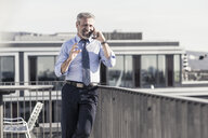 Smiling mature businessman on cell phone on roof terrace - UUF16714