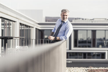 Smiling mature businessman standing on roof terrace - UUF16717