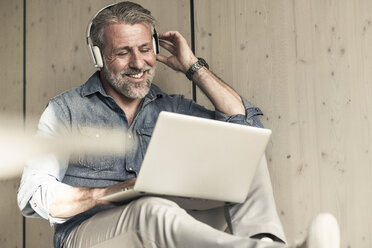 Casual mature businessman sitting down with laptop and headphones - UUF16726