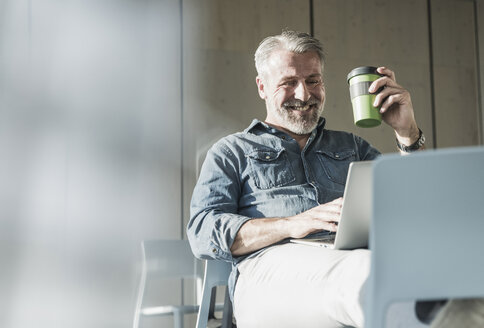Smiling casual mature businessman with laptop and takeaway coffee - UUF16735
