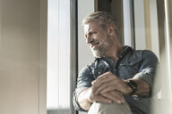 Smiling casual mature businessman looking out of window - UUF16744