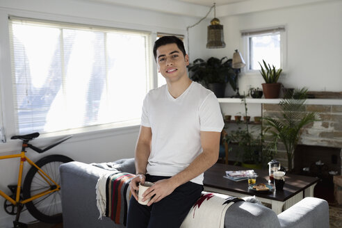 Portrait confident young Latinx man drinking coffee in living room - HEROF27974