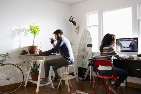 Creative freelance couple working in home office - HEROF27986