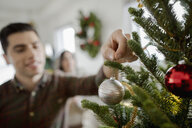 Young man hanging ornament on Christmas tree - HEROF28010
