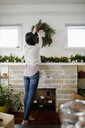 Young woman hanging Christmas wreath above fireplace - HEROF28013