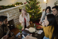 Friends playing cards in Christmas living room - HEROF28028
