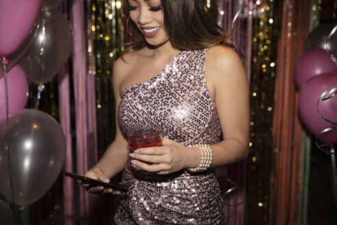 Woman in sequin dress drinking cocktail and using smart phone at party - HEROF28037