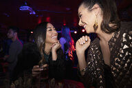 Happy women friends drinking in nightclub - HEROF28055