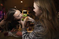 Women friends sharing hamburger at late night diner - HEROF28079