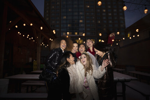 Portrait carefree bachelorette and friends on urban street at night - HEROF28100
