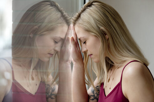 Deutschland,NRW,Ruhrgebiet,Stadt Essen,junge Frau spiegelt sich im Fenster - FLLF00062