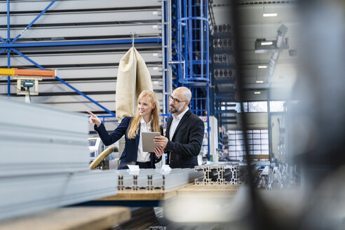 Businessman and businesswoman with tablet discussing in factory - DIGF06054