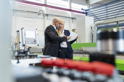 Businessman and businesswoman looking at plan in factory - DIGF06078