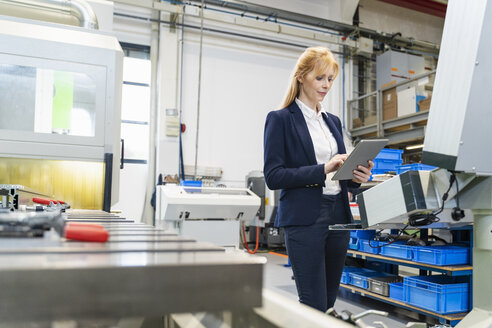 Businesswoman using tablet at machine in factory - DIGF06081