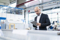 Businessman using tablet in factory - DIGF06144