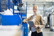 Businesswoman with tablet in factory storehouse - DIGF06165