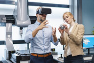 Businessman and businesswoman withVR glasses and workpiece in factory - DIGF06171
