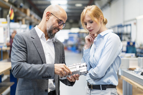 Businessman and businesswoman examining workpiece in factory - DIGF06174