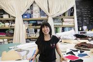 Portrait confident, smiling female fashion designer in studio - HEROF28193