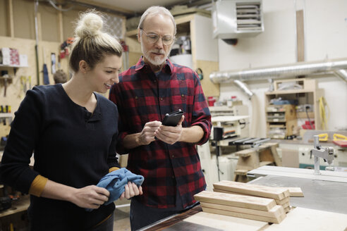 Father and daughter carpenters using smart phone in workshop - HEROF28280