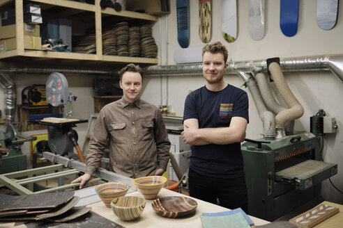 Portrait confident male artists with pottery bowls in workshop - HEROF28283