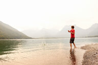 Young man skimming stone in Lake Annecy, Annecy, Rhone-Alpes, France - CUF49530